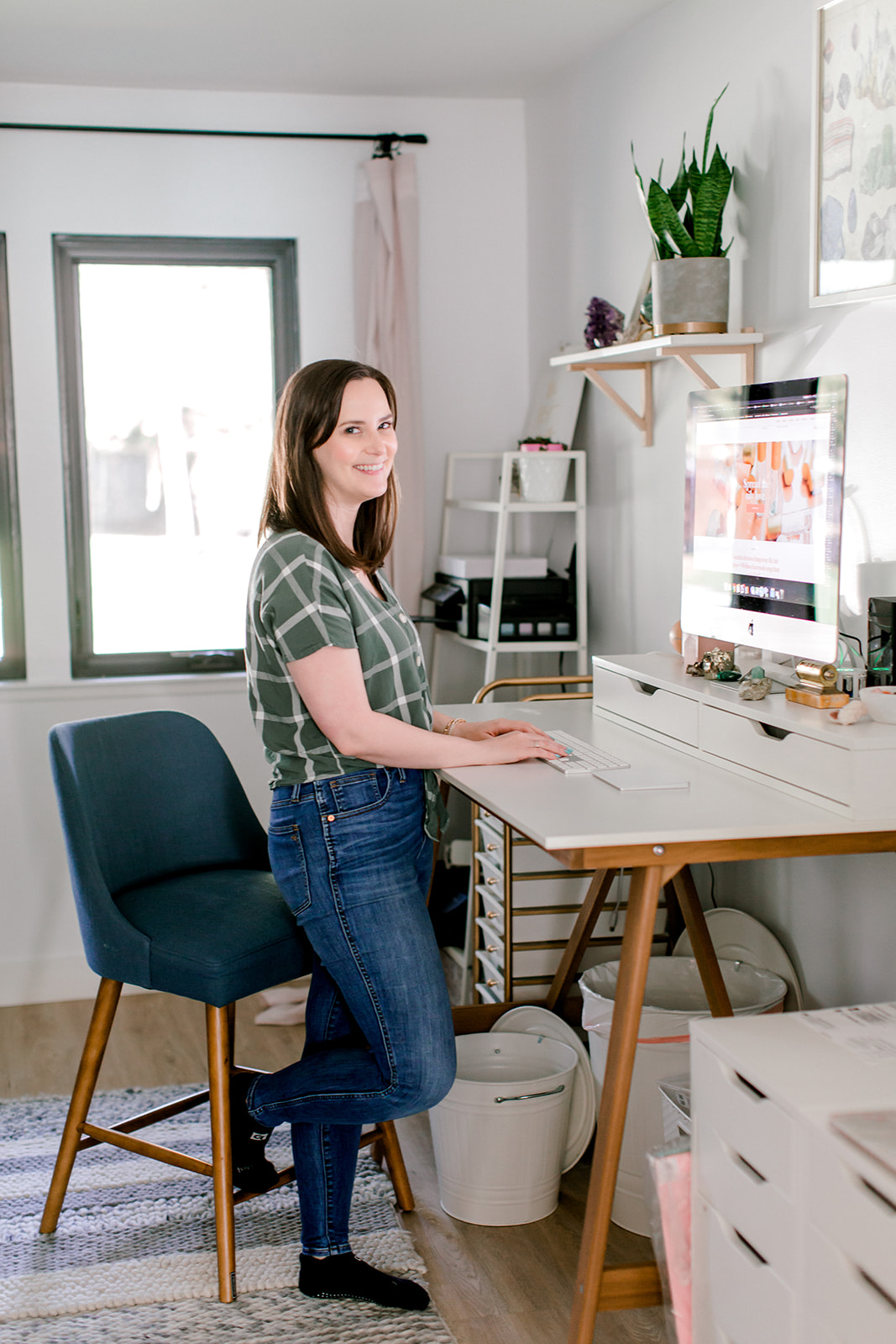 Haylee with her stand desk running Whimsy + Wellness from her home office