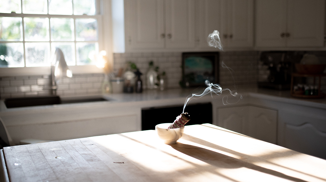 sage bundle burning to energetically clear home in kitchen
