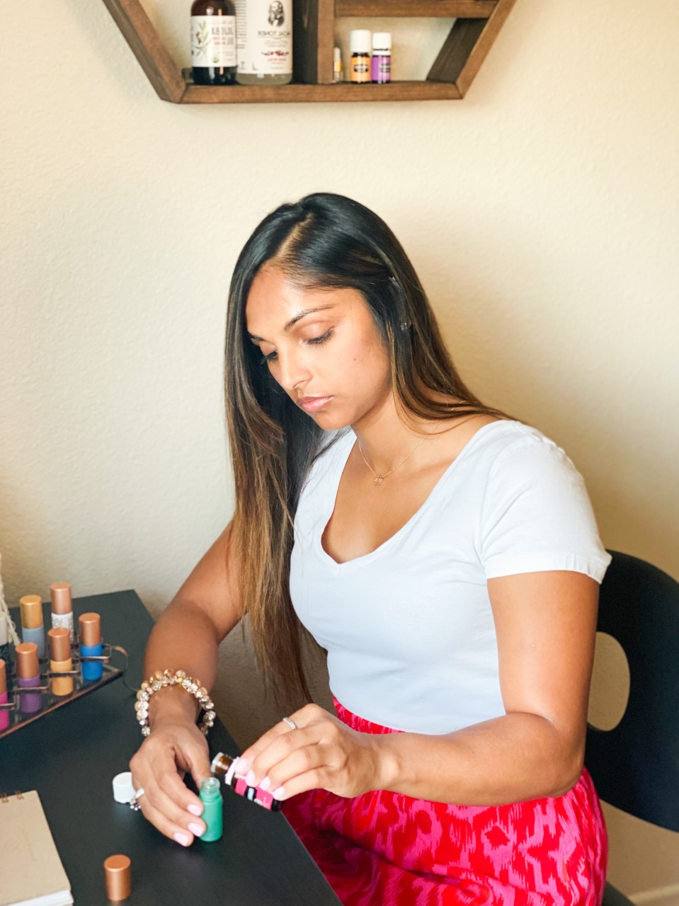 Anjali making essential oil recipes for her day, using Whimsy + Wellness roller bottles from the Bohemian Collection and Young Living Essential oils.
