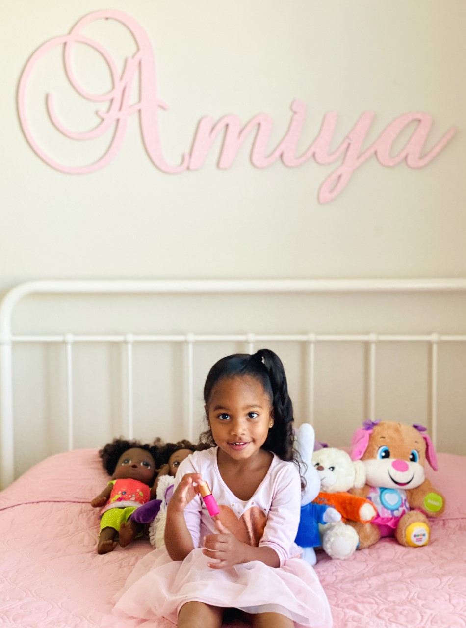 Anjali's daughter holds a 5ml pink roller bottle from the Whimsy + Wellness Bohemian Collection