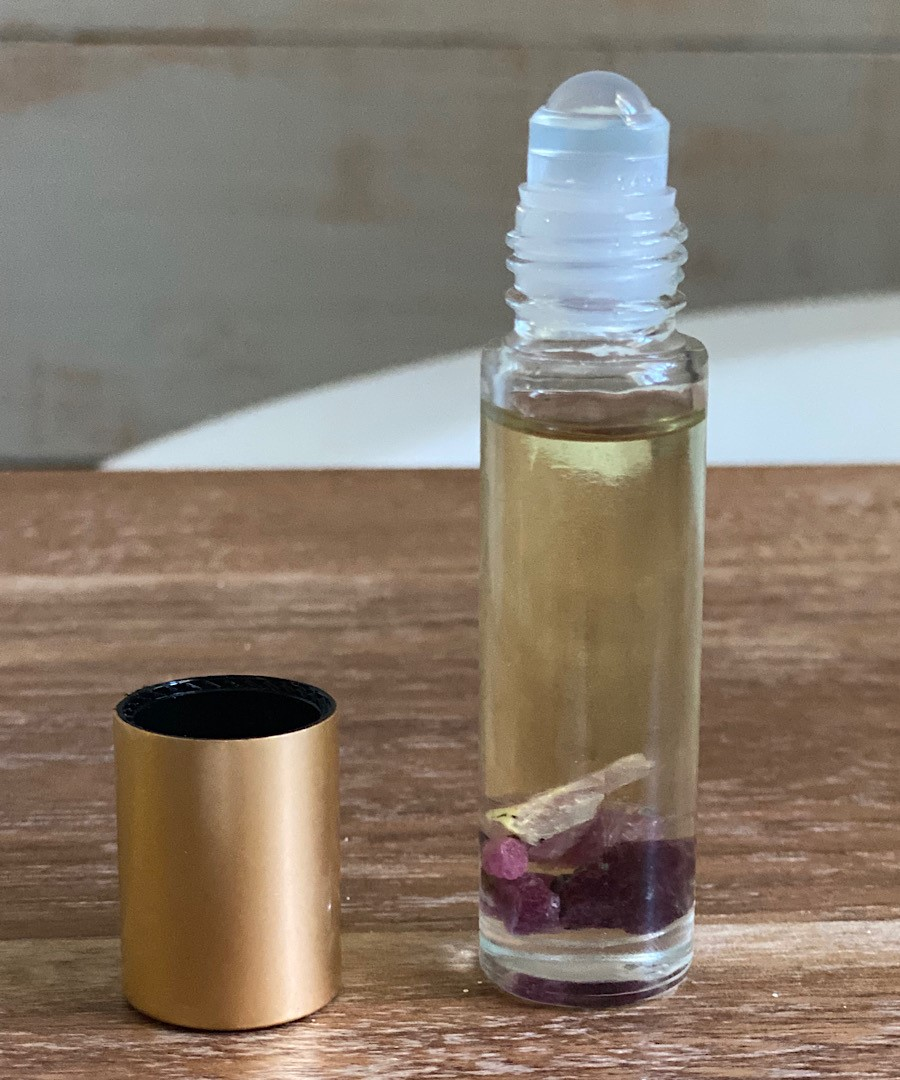 Caroline uses her doTERRA oils to fill a Whimsy + Wellness roller bottle with a Summertime perfume blend